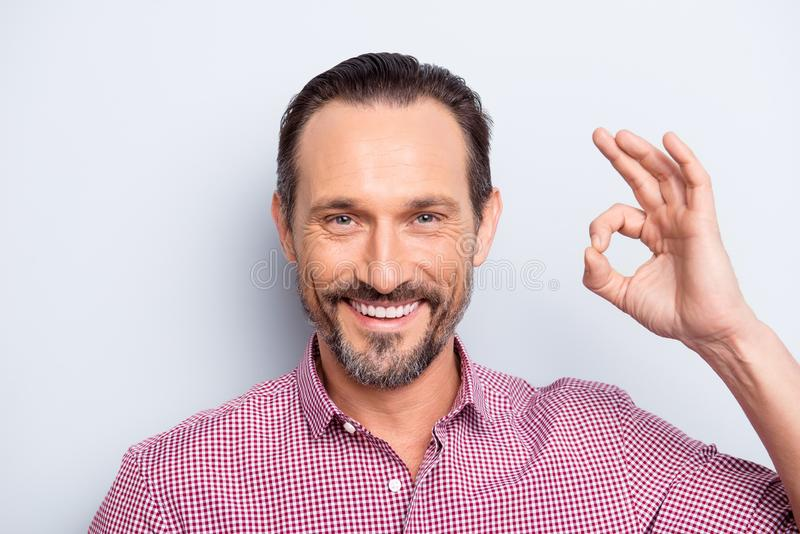 Portrait of good-looking man look at camera stand isolated on li. Ght gray background give ok sign make hollywood white smile stock photos