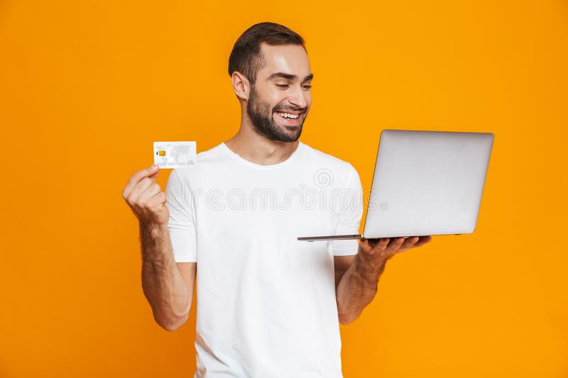 Portrait of good-looking man 30s in white t-shirt holding silver laptop and credit card, isolated over yellow background royalty free stock photo