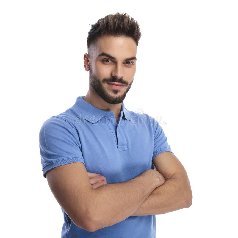 Portrait of a good-looking man wearing a blue polo. Holding his hands crossed on a light background stock image