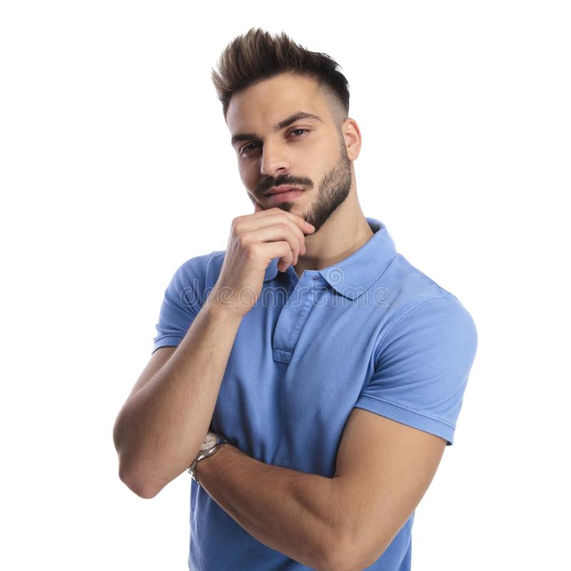 Portrait of a good-looking man wearing a blue polo. Portrait of a young good-looking man wearing a blue polo, holding his chin in a hand while looking at the royalty free stock images