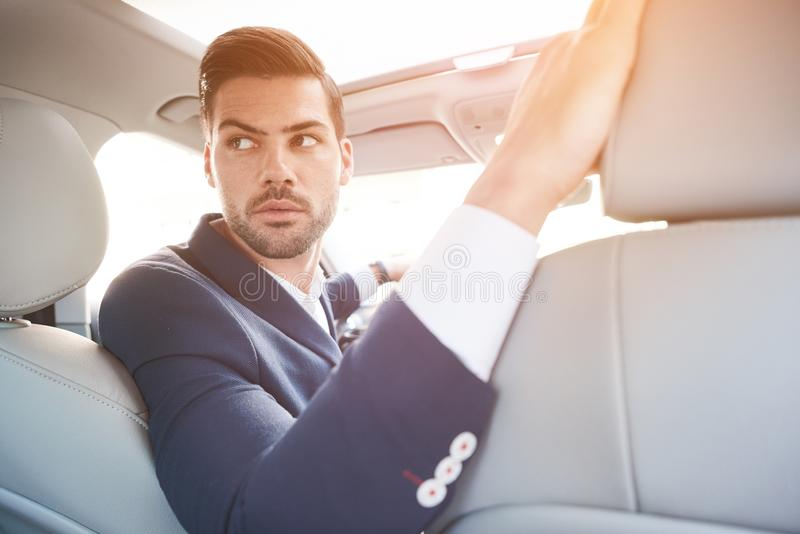 Portrait of good looking young man sitting in the driving seat o royalty free stock photos