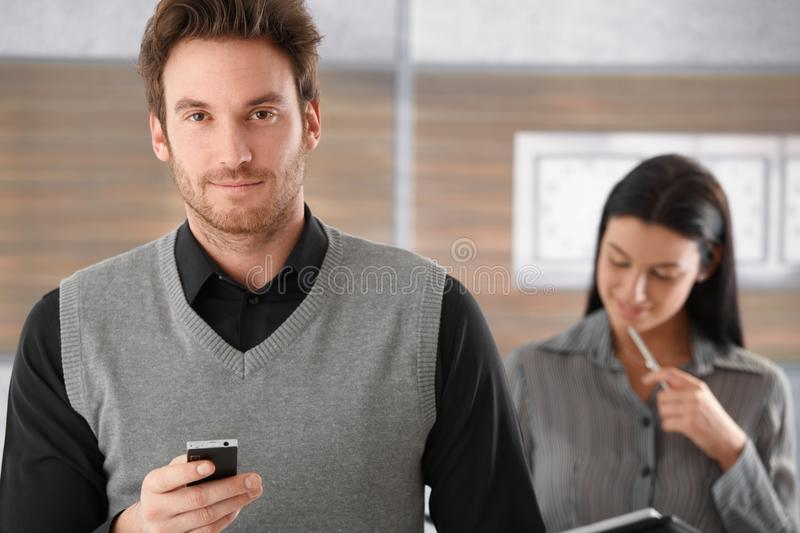 Portrait of goodlooking businessman with mobile. Phone, smiling stock images