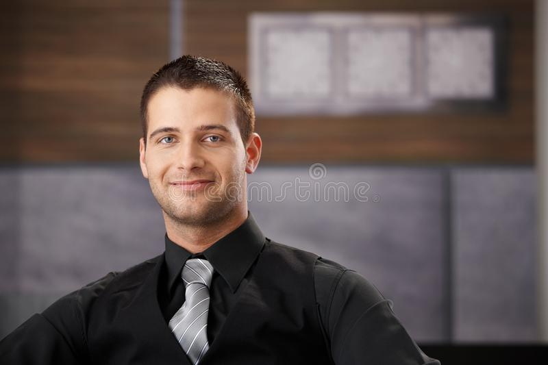 Portrait of goodlooking businessman smiling. Portrait of goodlooking young businessman sitting in fancy office, smiling stock photo