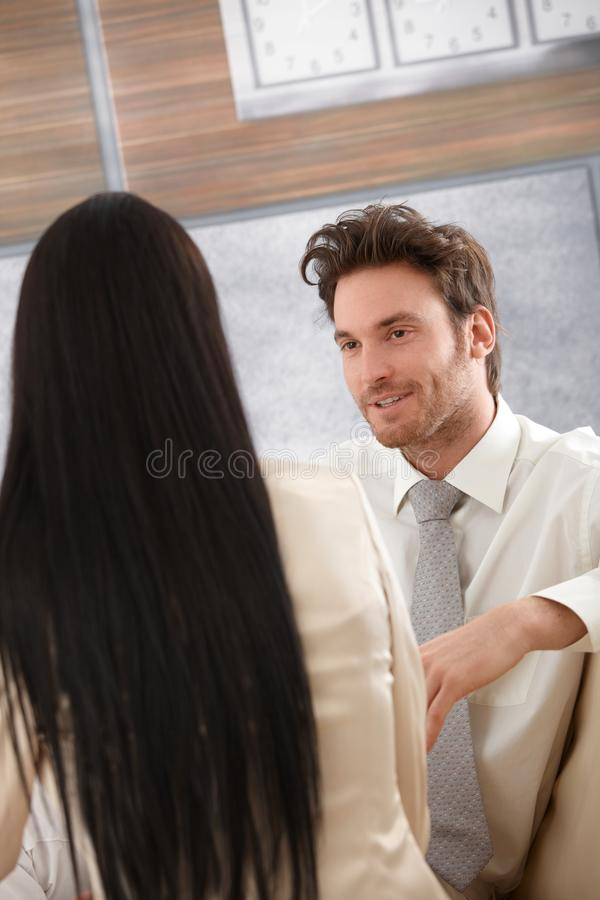 Portrait of goodlooking businessman smiling. Portrait of goodlooking businessman talking to female colleague, smiling stock image