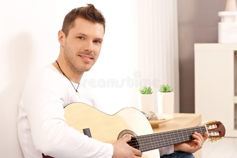 Portrait of goodlooking guitarist. Portrait of young goodlooking guitarist, playing guitar at home stock photos