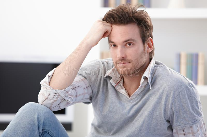 Portrait of goodlooking young man. Sitting at home on floor, smiling royalty free stock photos