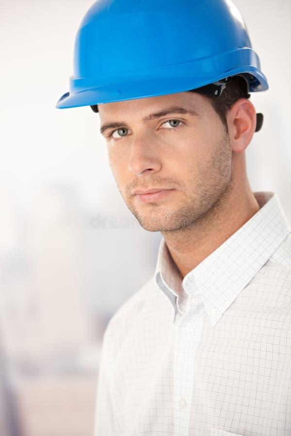 Portrait of goodlooking young man in helmet. Portrait of goodlooking young architect wearing helmet stock images