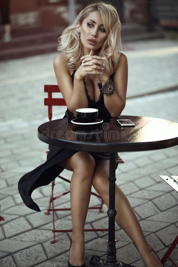 Portrait of gorgeous blond lady sitting alone in the open air cafe and looking aside thoughfully. Cup of coffee and mobile phone on the table in front of her royalty free stock photos