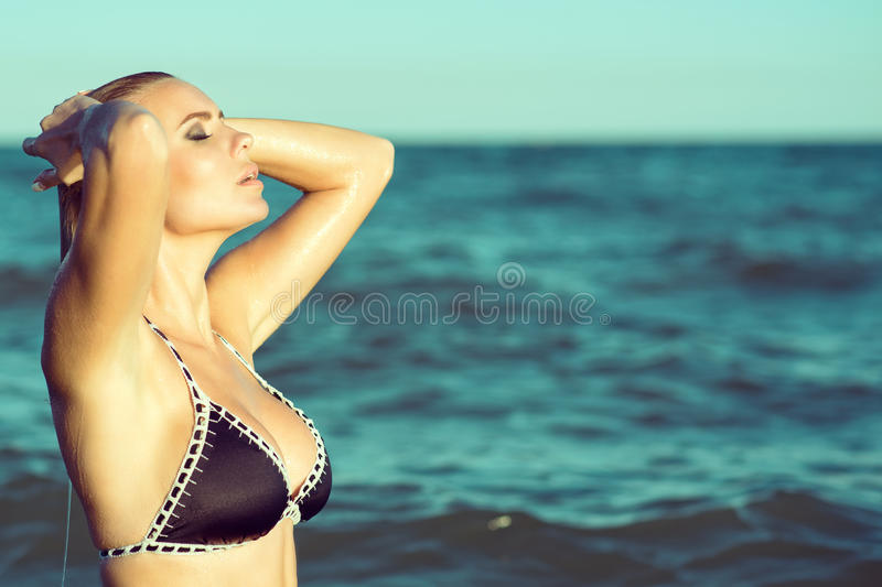Portrait of gorgeous blond woman in the swimsuit coming up from the sea with closed eyes and sleeking her wet hair. royalty free stock photography
