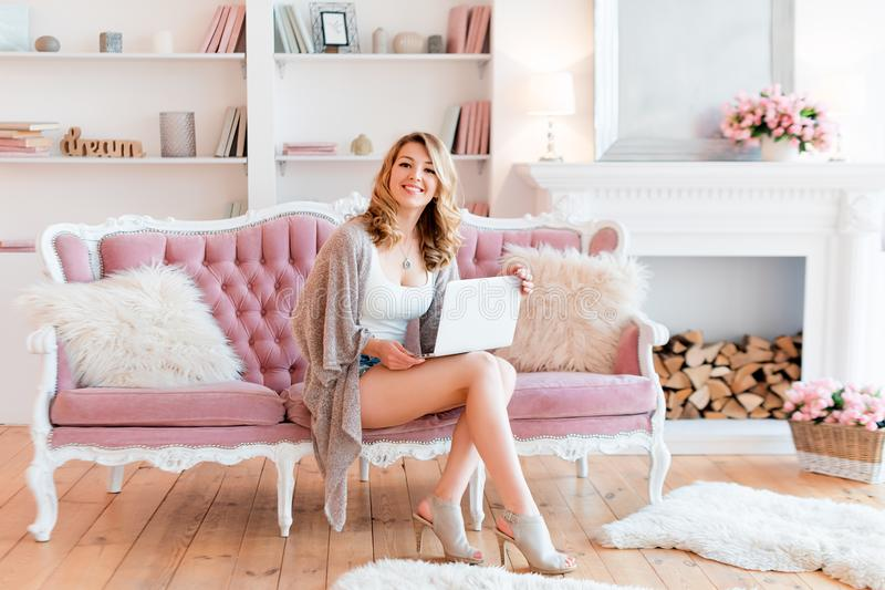 Portrait of gorgeous blonde woman with laptop working at home. Woman sitting on pink sofa in light luxury interior with stock images