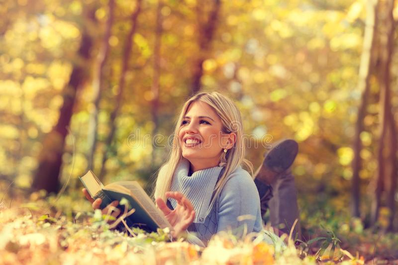 Portrait of a gorgeous blonde woman reading a book in the autumn park stock photo