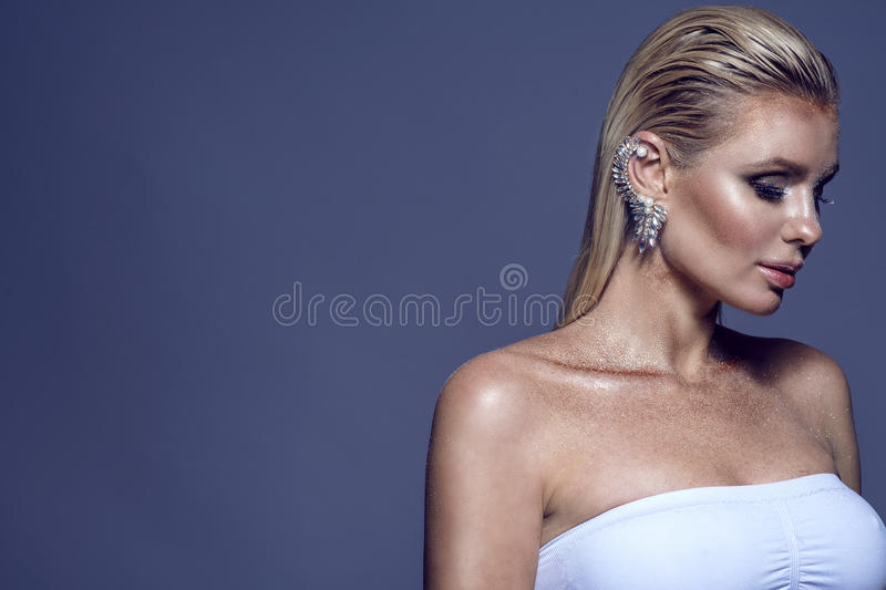 Portrait of gorgeous chic blond woman with wet hair and shining artistic make-up wearing white top and precious cuff in her ear stock photography