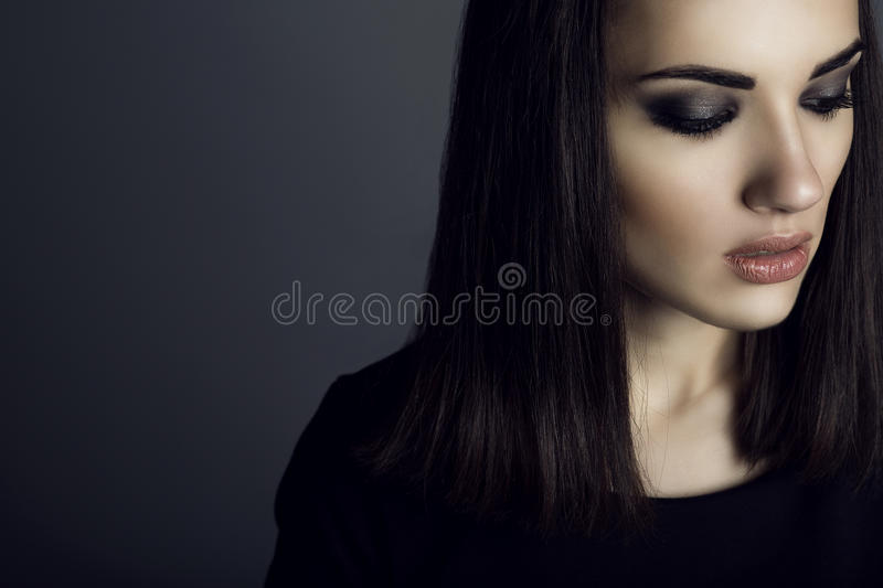 Portrait of gorgeous dark-haired woman with provocative make up looking down with sad expression on her face. royalty free stock image
