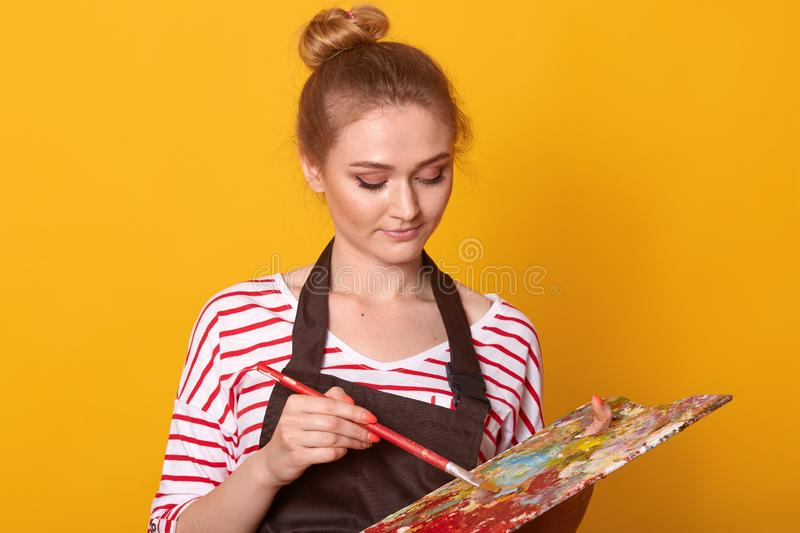 Portrait of gorgeous female artist drawing picrure, adorable girl holding brush and palette of colours in hands, young woman stock photography