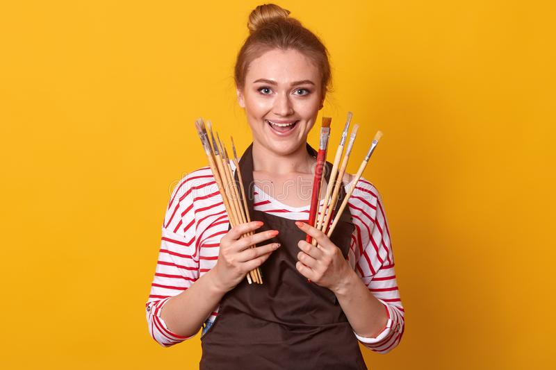 Portrait of gorgeous female artist working on art projects, attractive woman wearing striped casual shirt and brown apron, royalty free stock photos