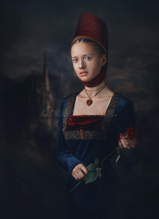 Portrait of a gorgeous girl in medieval era dress and headdress. Medallion in a shape of heart. Holding red rose in hands. stock images