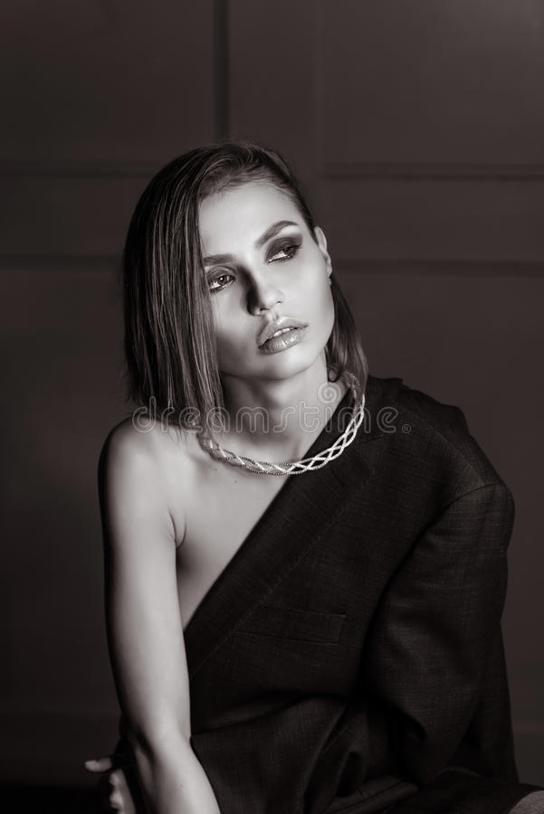 Portrait of a gorgeous girl in the studio in a man's jacket, a necklace with short wet hair does not look at the camera in BW stock image