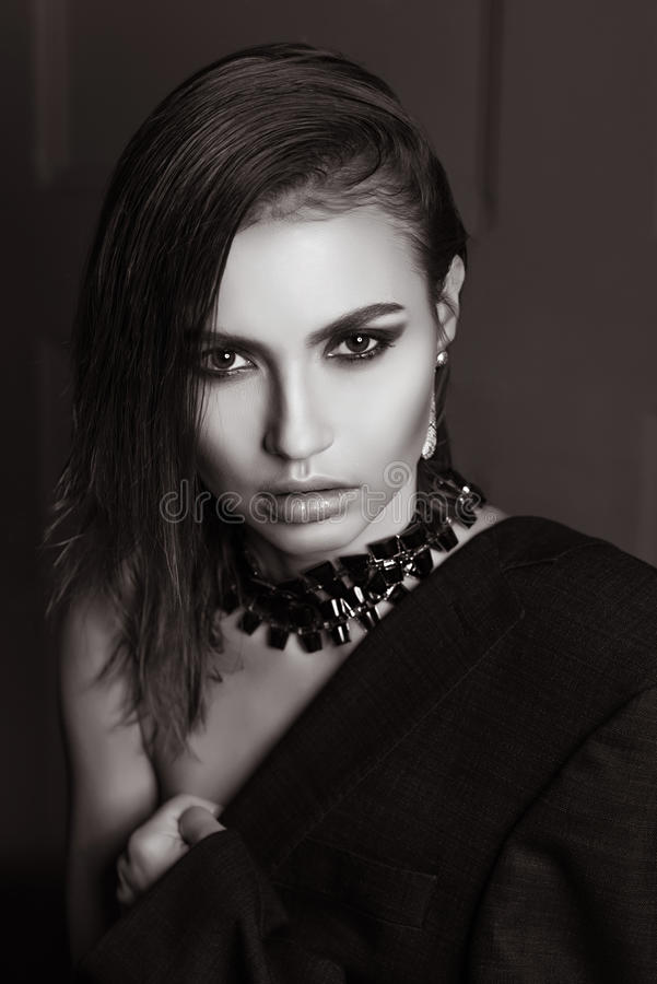 Portrait of a gorgeous girl in the studio in a man's jacket, a necklace with short wet hair looking at the camera in BW royalty free stock photo