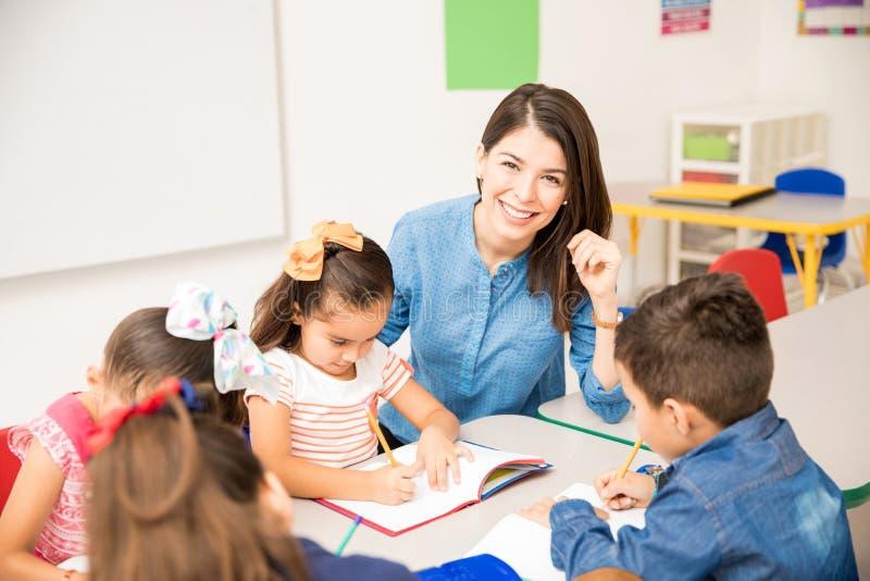 Beautiful preschool teacher during class stock images