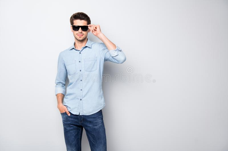 Portrait of gorgeous rich wealthy macho man touch his eyewear attract girls best guy in university wear denim jeans. Portrait of gorgeous rich wealthy macho man royalty free stock image
