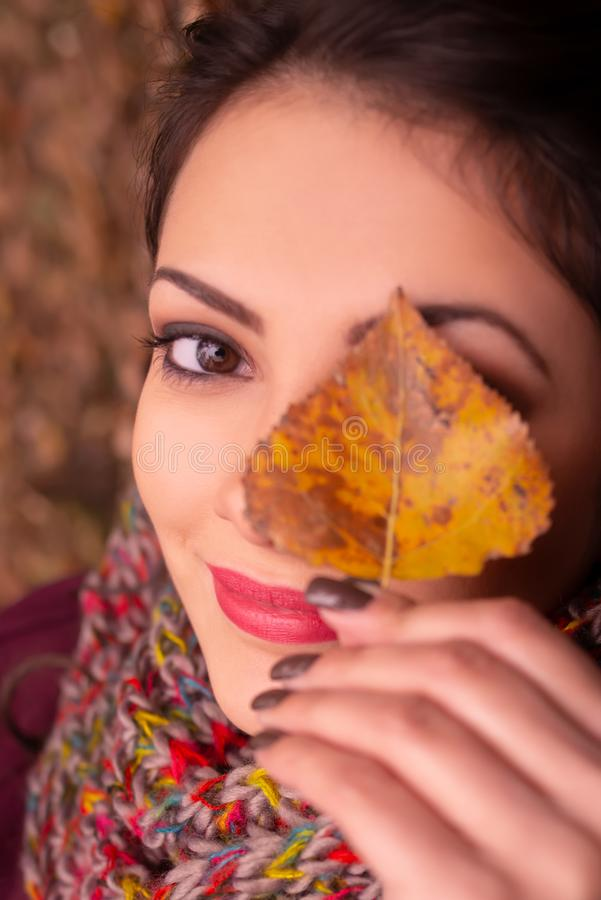 Portrait of a gorgeous romantic young woman holding an autumn leaf in front of her left eye, smiling subtly at the royalty free stock photos