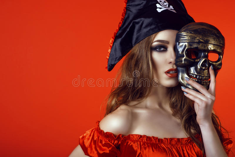 Portrait of gorgeous woman with provocative make-up in pirate costume hiding the half of her face behind skull mask royalty free stock images
