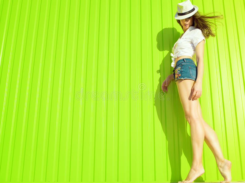 Portrait of gorgeous slim long-legged model with long waving hair wearing white panama, blouse and trendy jeans shorts. With flower ornament. on light green royalty free stock image