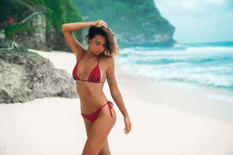 Portrait of a gorgeous woman in a red bikini on the beach with white sand. Beautiful girl with a tanned body on a royalty free stock images
