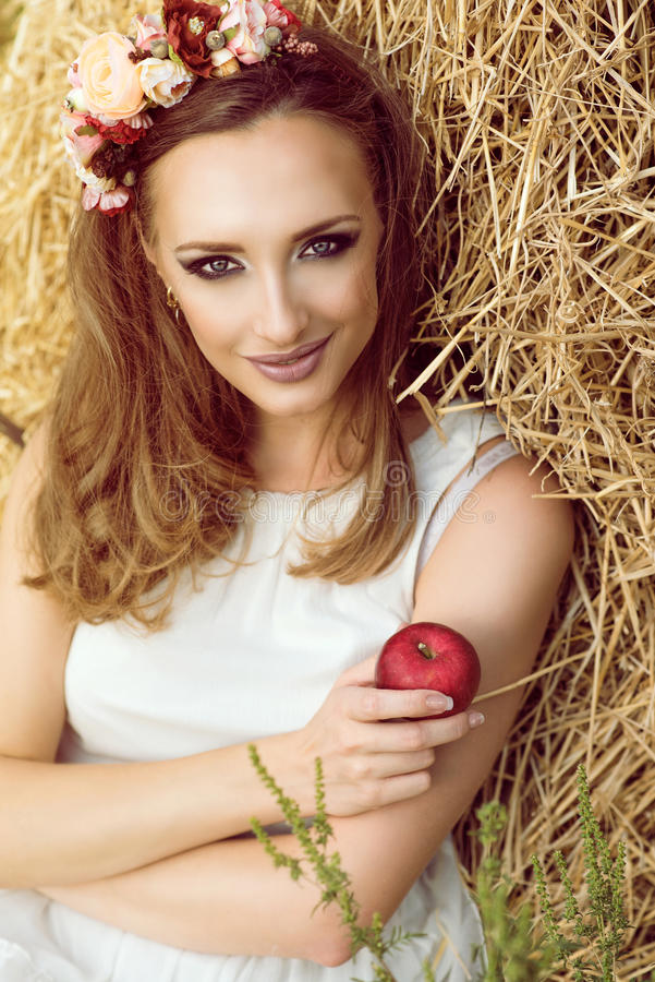 Portrait of gorgeous woman in white sundress sitting at the haystack with garland of flowers on her head, holding a red apple stock photo