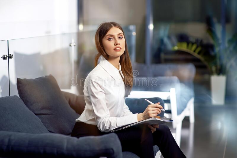 Portrait of gorgeous young businesslady in glasses sitting at her workplace in the office royalty free stock photos