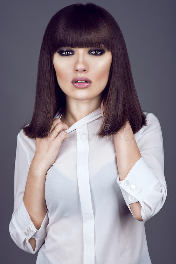 Portrait of gorgeous young dark-haired woman looking straight and pulling the collar of her blouse with tired look stock photography