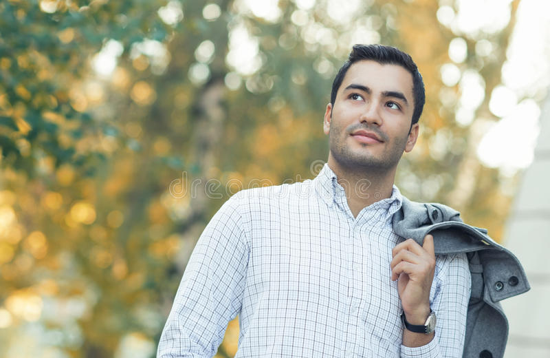 Portrait of gorgeous young hispanic man. Outdoor - outside. Guy in shirt with coat over his shoulder posing in a forest. Autumn beautiful day stock photo
