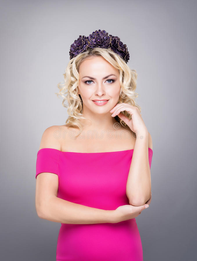 Portrait of gorgeous, young lady wearing pink dress and purple wreath stock image