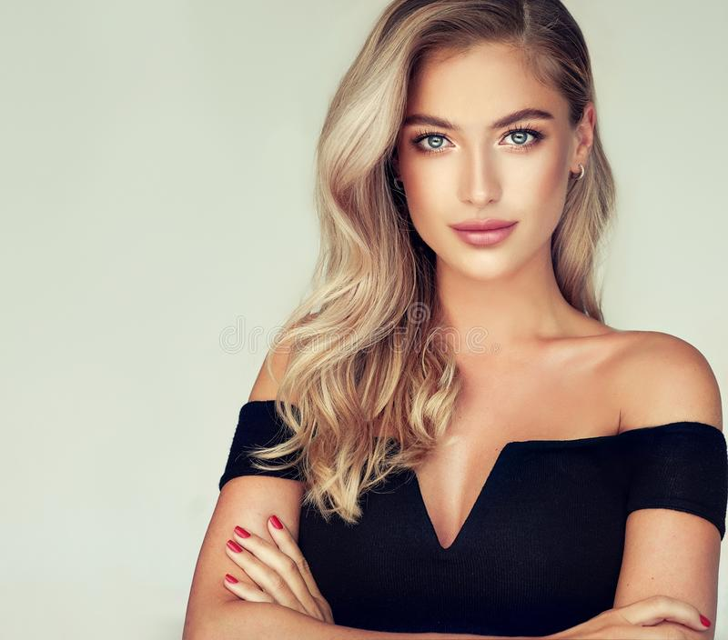 Portrait of gorgeous young woman with elegant make up and perfect golden hairstyle. Young golden haired pretty model tenderly looking ot viewers with light stock images