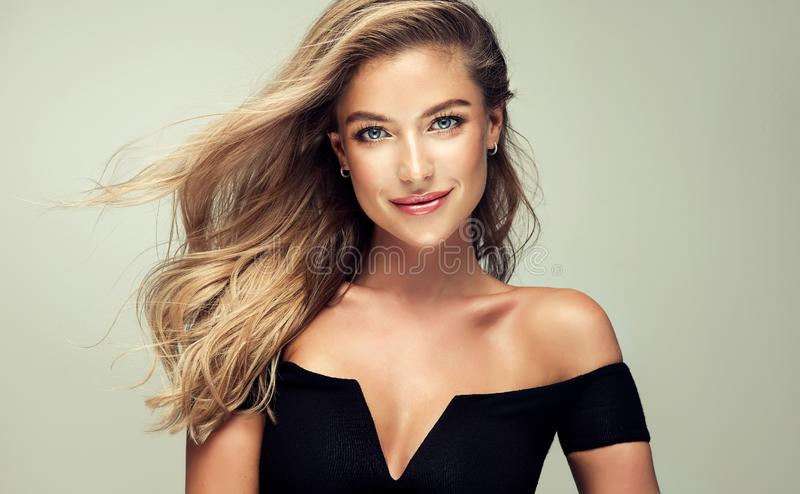 Portrait of gorgeous young woman with elegant make up and perfect golden hairstyle. Young golden haired pretty model tenderly looking ot viewers with light stock photo