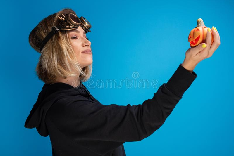 Portrait of goth girl wearing steam punk glasses looking confident at an orange carved pumpkin royalty free stock photos