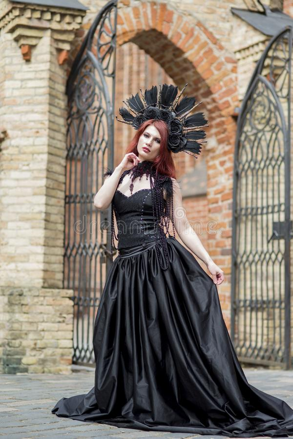 Portrait of Gothic Caucasian Woman in Black Dress and Artistic Feather Crown. posing Against Old Castle Gates. Vertical Image stock photos