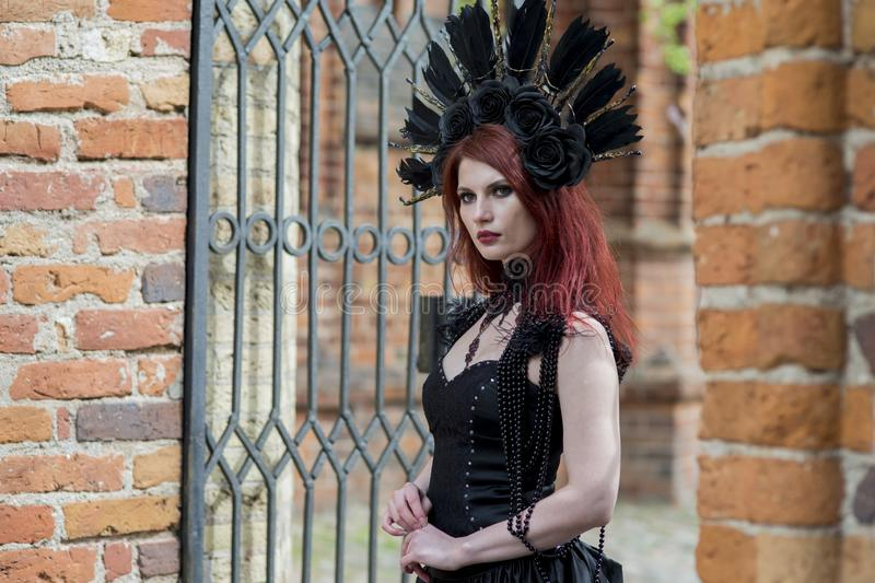 Portrait of Gothic Caucasian Woman in Black Dress and Artistic Feather Crown. posing Against Old Castle Gates. Horizontal Image royalty free stock images