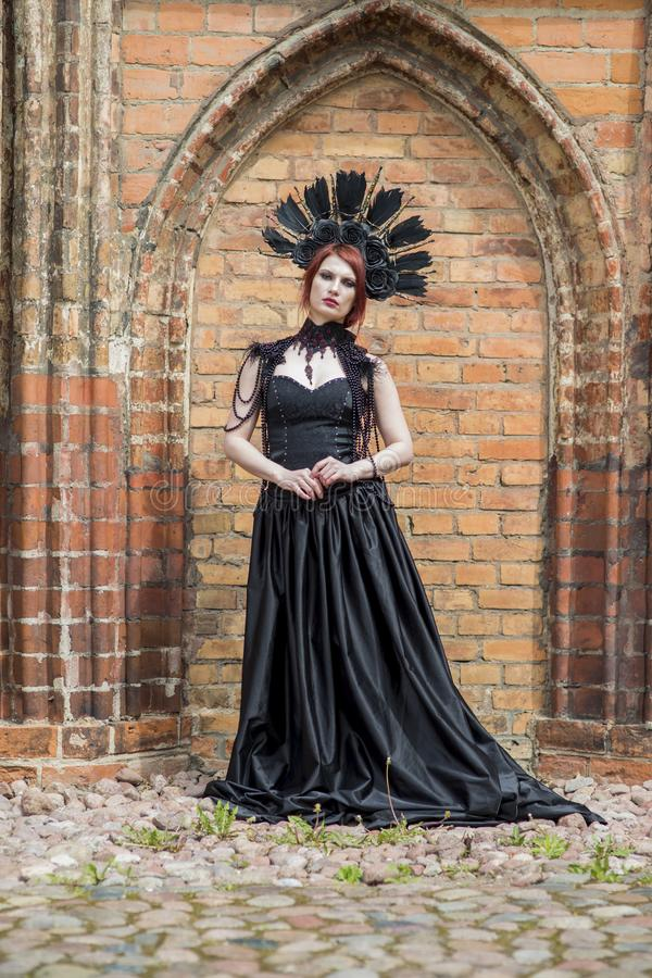 Portrait of Gothic Caucasian Woman in Black Flying Dress. Wearing Artistic Feather Crown. Posing Against Old Castle Gates. Portrait of Gothic Caucasian Woman in stock photo