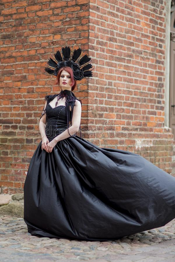 Portrait of Gothic Caucasian Woman in Black Flying Dress. Wearing Artistic Feather Crown. Posing Against Old Castle Gates. Vertical Image Composition stock images