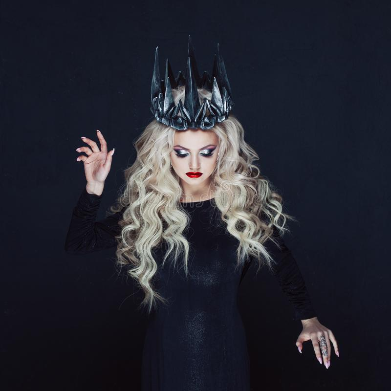 Portrait of a Gothic Princess. Beautiful young blonde woman in metal crown and black cloak. Mystical image stock photo