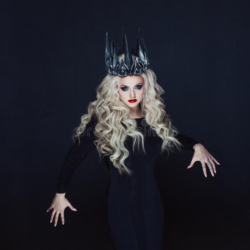 Portrait of a Gothic Princess. Beautiful young blonde woman in metal crown and black cloak. Mystical image royalty free stock photo