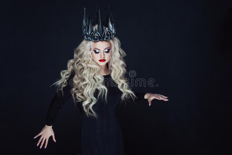Portrait of a Gothic Princess. Beautiful young blonde woman in metal crown and black cloak. Mystical image stock photos