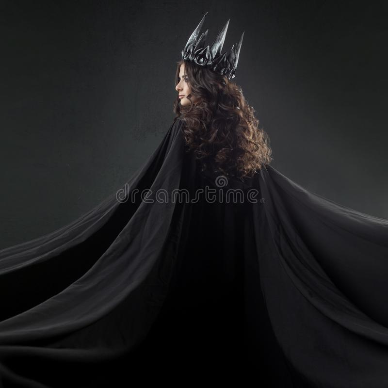 Portrait of a Gothic Princess. Beautiful young brunette woman in metal crown and black cloak. Mystical image royalty free stock image