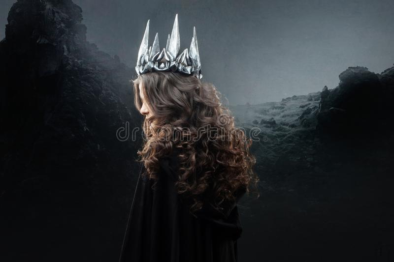 Portrait of a Gothic Princess. Beautiful young brunette woman in metal crown and black cloak. royalty free stock photos