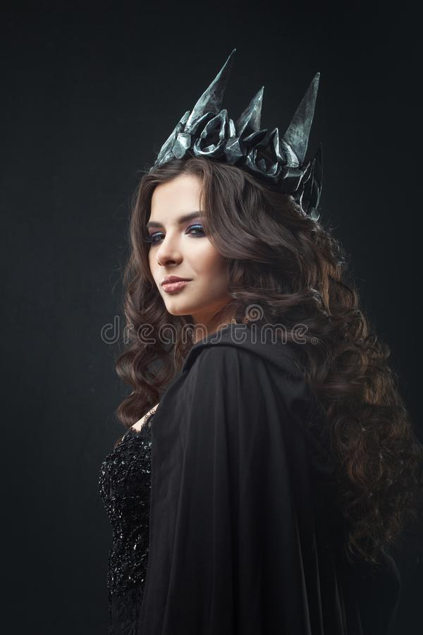 Portrait of a Gothic Princess. Beautiful young brunette woman in metal crown and black cloak. Mystical image stock photos