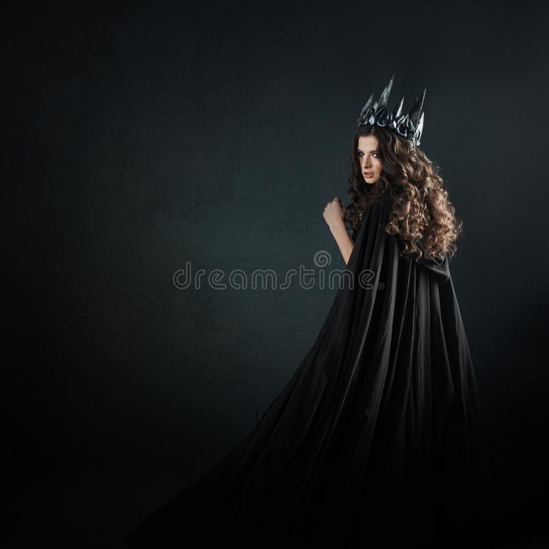 Portrait of a Gothic Princess. Beautiful young brunette woman in metal crown and black cloak. Mystical image royalty free stock photo