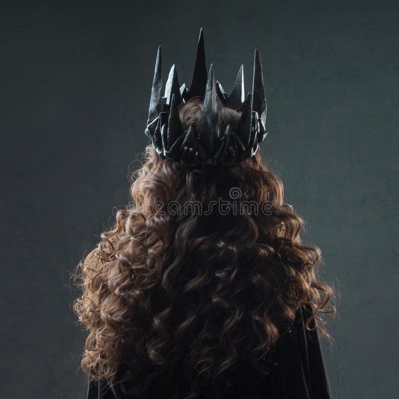 Portrait of a Gothic Princess. Beautiful young brunette woman in metal crown and black cloak. Back view royalty free stock photos