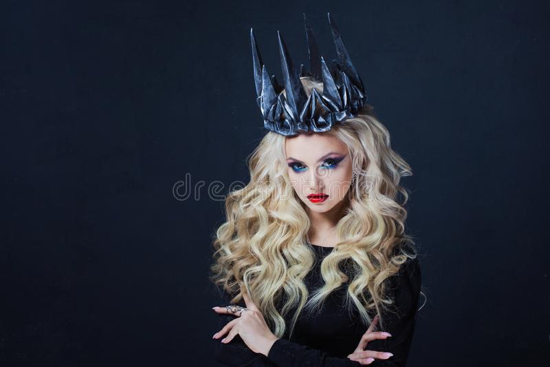 Portrait of a Gothic Queen. Beautiful young blonde woman in metal crown and black cloak. Mystical image stock photography