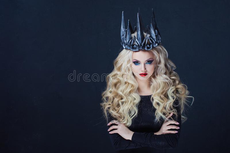 Portrait of a Gothic Queen. Beautiful young blonde woman in metal crown and black cloak. Mystical image royalty free stock image